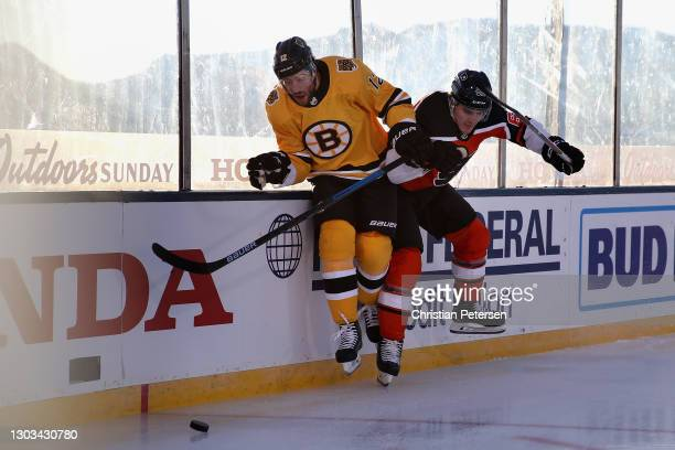 Nicolas Aube-Kubel of the Philadelphia Flyers lays a body check on Craig Smith of the Boston Bruins during the first period of the 'NHL Outdoors At...