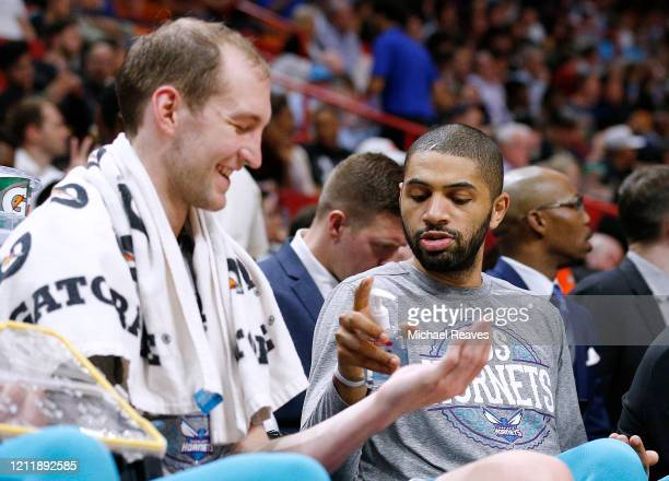 Nicolas Batum of the Charlotte Hornets gives Cody Zeller hand sanitizer during the second half against the Miami Heat at American Airlines Arena on...