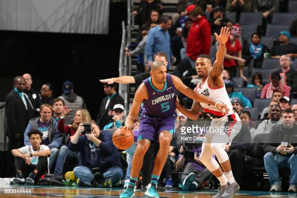 Nicolas Batum of the Charlotte Hornets handles the ball against Damian Lillard of the Portland Trail Blazers on December 16 2017 at Spectrum Center...