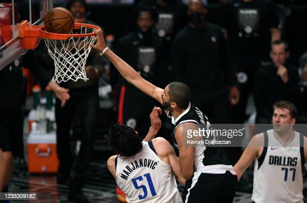 Nicolas Batum of the Los Angeles Clippers dunks the ball against Boban Marjanovic of the Dallas Mavericks during the first half of Game Seven of the...