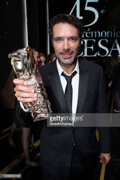 """Nicolas Bedos poses with the """"Best Original Screenplay"""" award for the movie 'La Belle Époque' during the Cesar Film Awards 2020 Ceremony at Salle..."""