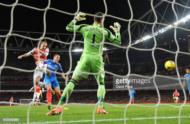 Nicolas Bendtner scores Arsenal's 1st goal past Allan McGregor and under pressure from James Chester of Hull City during the Premier League match...