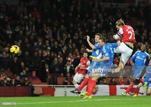 Nicolas Bendtner scores Arsenal's 1st goal past under pressure from James Chester and Alex Bruce of Hull City during the Premier League match between...