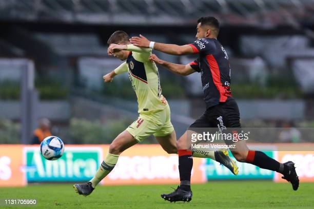 Nicolas Benedetti of America struggle for the ball against Jose Esquivel of Lobos BUAP during the 8th round match between America and Lobos BUAP as...