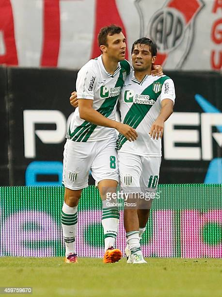 Nicolas Bertolo of Banfield celebrates with Walter Erviti after scoring the first goal of his team during a match between Banfield and River Plate as...