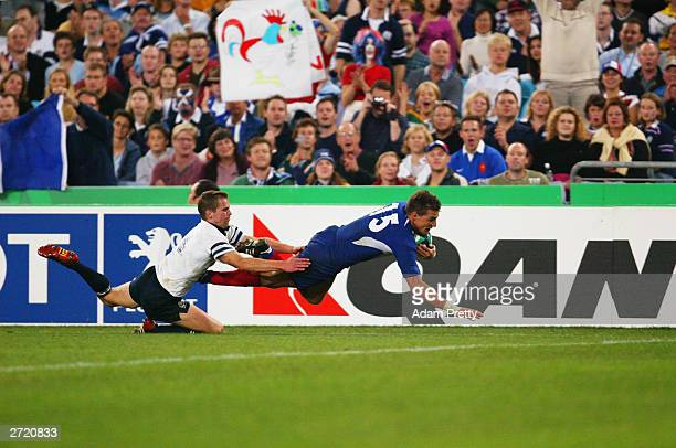 Nicolas Brusque of France dives over to score a try despite an attempted tackle from Chris Paterson of Scotland during the Rugby World Cup Pool B...