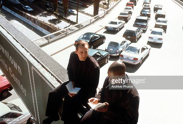 Nicolas Cage and Andre Braugher are sitting on a freeway overpass sign with heavy traffic below them in a scene from the film 'City Of Angels' 1998