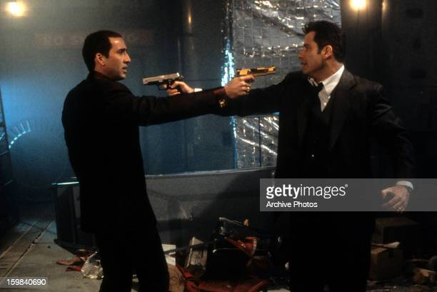Nicolas Cage and John Travolta aiming guns at each other in a scene from the film 'Face/Off' 1997