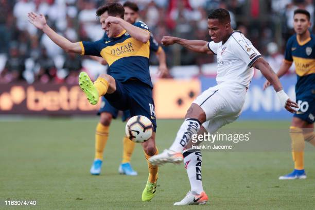 Nicolas Capaldo of Boca Juniors fights for the ball with Antonio Valencia of Liga de Quito during a match between Liga Deportiva Universitaria and...