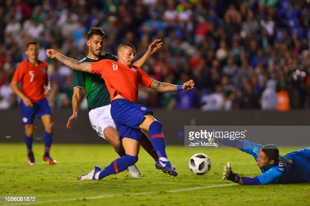 Nicolas Castillo of Chile kicks the ball to score a goal over goalkeeper Hugo Gonzalez of Mexico during the international friendly match between...