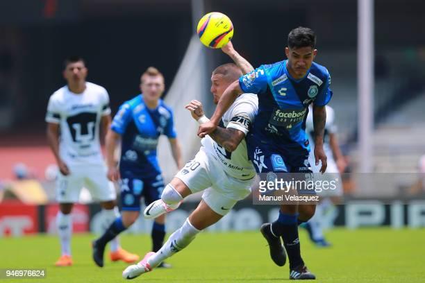 Nicolas Castillo of Pumas struggles for the ball against Anderson Santamaria of Puebla during the 15th round match between Pumas UNAM and Puebla as...