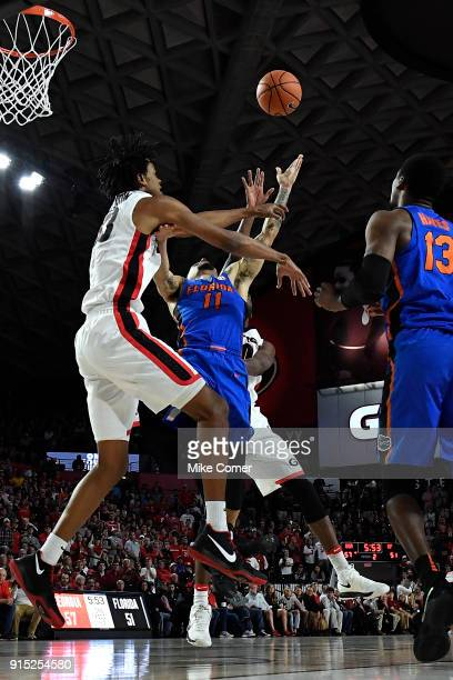 Nicolas Claxton of the Georgia Bulldogs defends as Chris Chiozza of the Florida Gators drives to the basket during the basketball game at Stegeman...