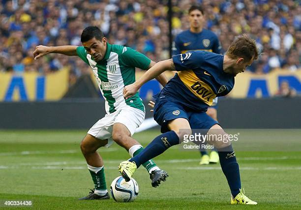 Nicolas Colazo of Boca Juniors battles for the ball with Walter Erviti of Banfield during a match between Boca Juniors and Banfield as part of 26th...