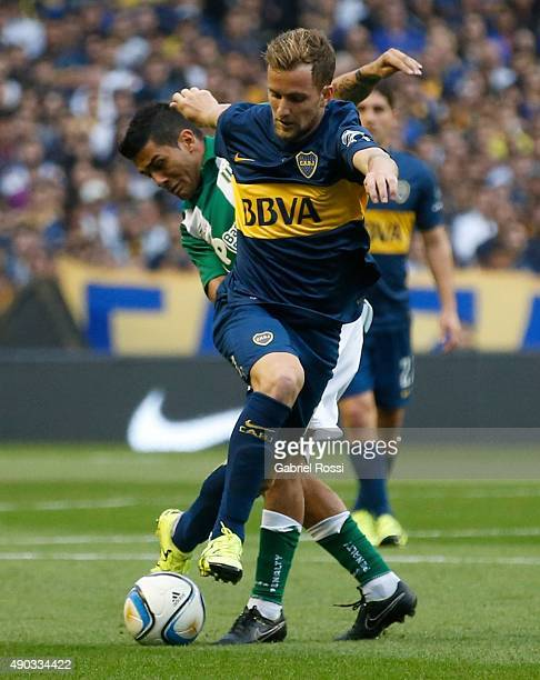 Nicolas Colazo of Boca Juniors fights for the ball with Walter Erviti of Banfield during a match between Boca Juniors and Banfield as part of 26th...