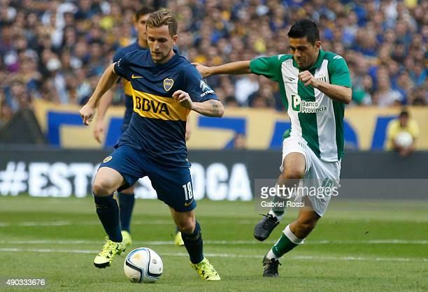 Nicolas Colazo of Boca Juniors struggles for the ball with Walter Erviti of Banfield during a match between Boca Juniors and Banfield as part of 26th...