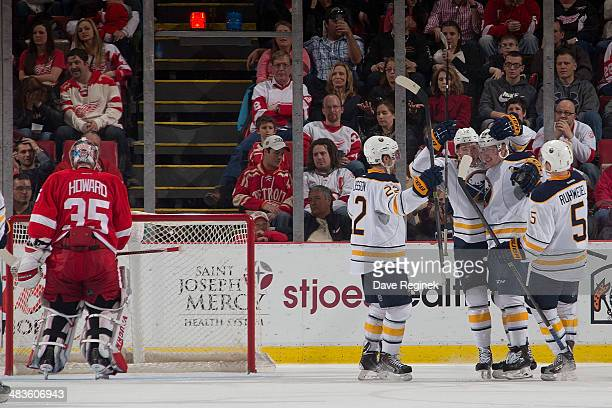Nicolas Deslauriers of the Buffalo Sabres celebrates his first NHL goal with teammates Chad Ruhwedel Johan Larsson and Luke Adam as goaltender Jimmy...
