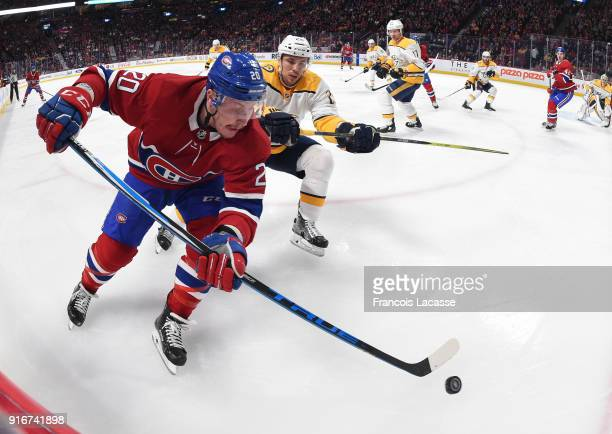 Nicolas Deslauriers of the Montreal Canadiens skates with the puck under pressure from Alexei Emelin of the Nashville Predators in the NHL game at...
