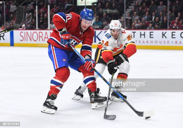 Nicolas Deslauriers tries to keep the puck from Travis Hamonic of the Montreal Canadiens of the Calgary Flames in the NHL game at the Bell Centre on...