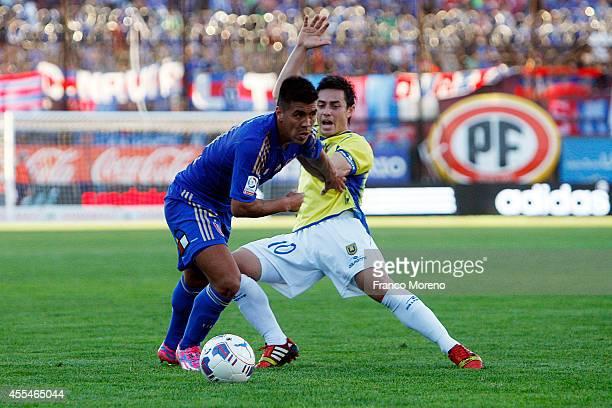 Nicolas Espinoza of U de Chile fights for the ball with Marcelo Aguirre of U de Concepcion during a match between U de Chile and U de Concepcion as...