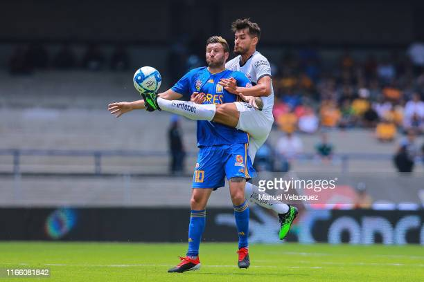 Nicolas Freire of Pumas struggles for the ball against Andre-Pierre Gignac of Tigres during the 3rd round match between Pumas UNAM and Tigres UANL as...