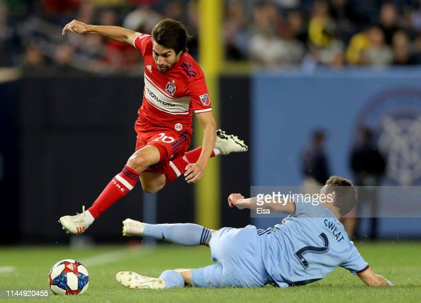 Nicolas Gaitan of Chicago Fire avoids the tackle by Ben Sweat of New York City FC at Yankee Stadium on April 24, 2019 in the Bronx borough of New...