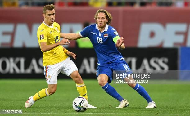 Nicolas Hasler of Liechtenstein vies for the ball with R?zvan Marin of Romania during the FIFA World Cup Qatar 2022 qualification Group J football...