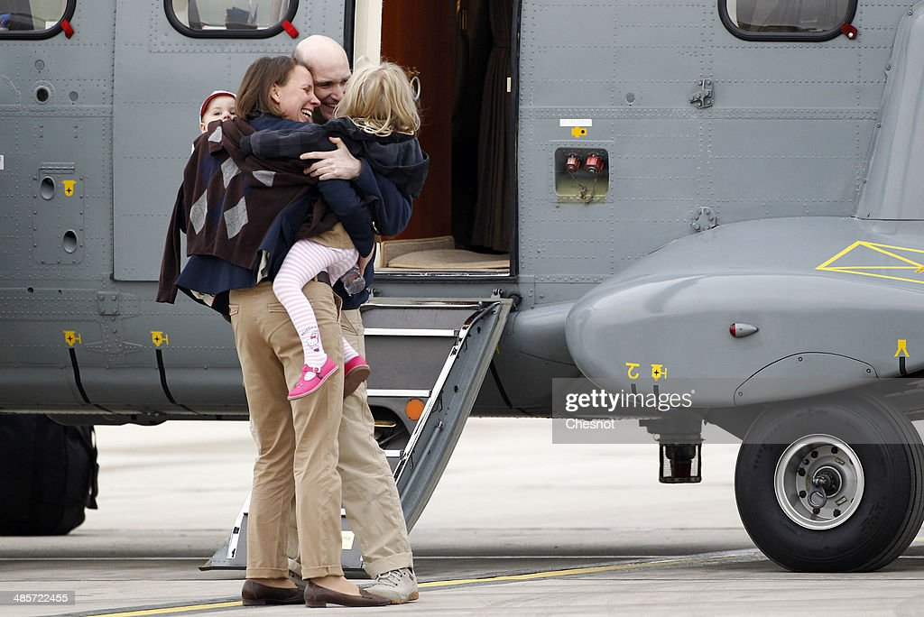 Nicolas Henin (C) is welcomed by his family and relatives upon his arrival at the Villacoublay military airport on April 20, 2014 in Velizy-Villacoublay, France. The four French journalists taken hostage in Syria last year were freed after a 10-month captivity in the world's most dangerous country for the media.