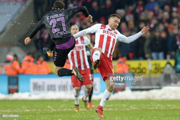 Nicolas Hoefler of Freiburg and Christian Clemens of Koeln battle for the ball during the Bundesliga match between 1 FC Koeln and SportClub Freiburg...