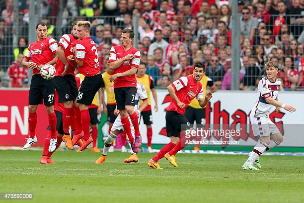 Nicolas Hoefler of Freiburg and his team mates jumps at the wall during the Bundesliga match between Sport Club Freiburg and FC Bayern Muenchen at...
