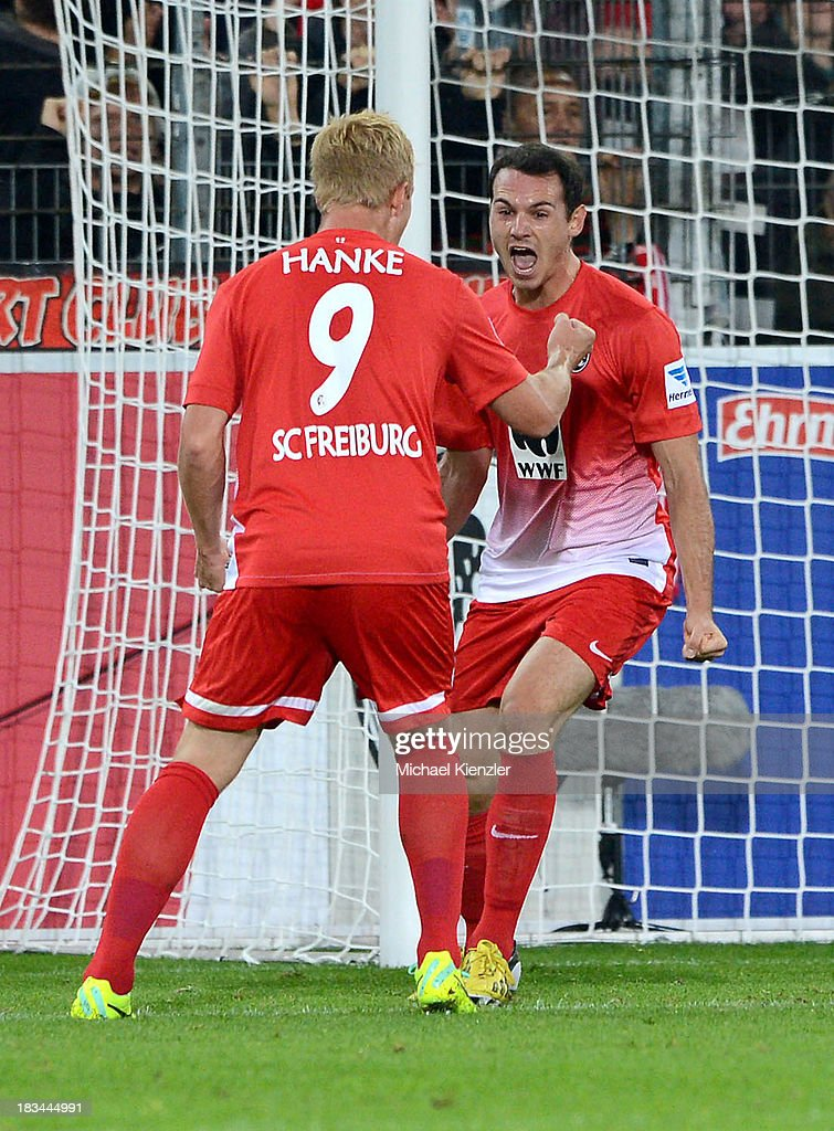 Nicolas Hoefler (R) of Freiburg celebrates with team-mate and Mike Hanke after scoring the team's first goal during the Bundesliga match between SC Freiburg and Eintracht Frankfurt at Mage Solar Stadium on October 6, 2013 in Freiburg, Germany.