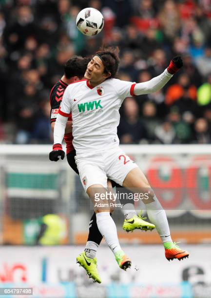 Nicolas Hoefler of Freiburg challenges Ji DongWon of Augsburg during the Bundesliga match between FC Augsburg and SC Freiburg at WWK Arena on March...