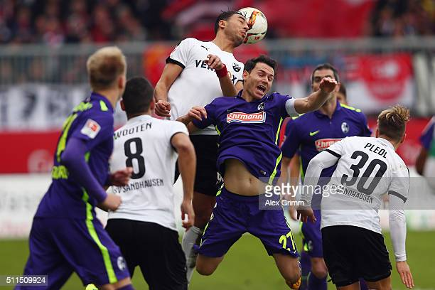 Nicolas Hoefler of Freiburg is challenged by Aziz Bouhaddouz of Sandhausen during the Second Bundesliga match between SV Sandhausen and SC Freiburg...