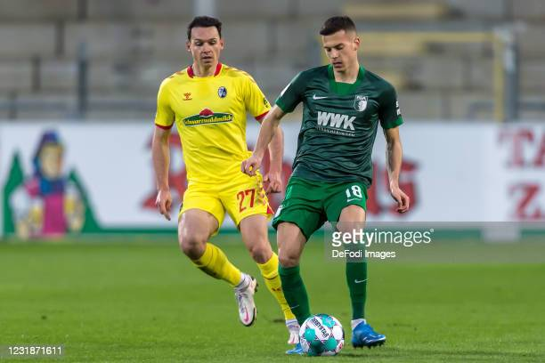 Nicolas Hoefler of SC Freiburg and Laszlo Benes of FC Augsburg battle for the ball during the Bundesliga match between Sport-Club Freiburg and FC...