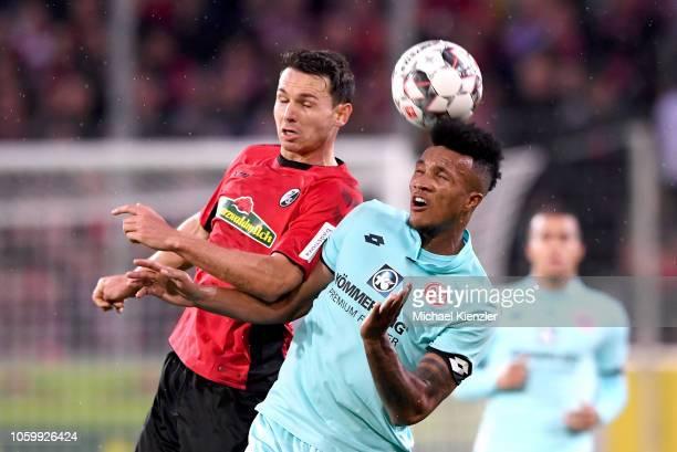 Nicolas Hoefler of SC Freiburg challenges Jean-Philippe Gbamin of FSV Mainz 05 during the Bundesliga match between Sport Club Freiburg and Mainz 05...