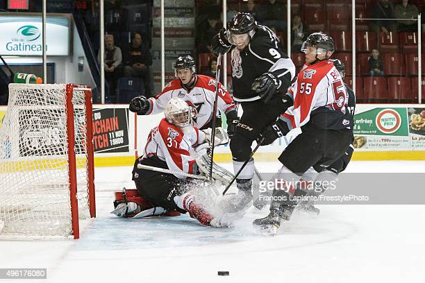 Nicolas Lachance of the Drummondville Voltigeurs makes a save as Sergei Boikov and Frederic Aube defend against Yan Pavel Laplante of the Gatineau...
