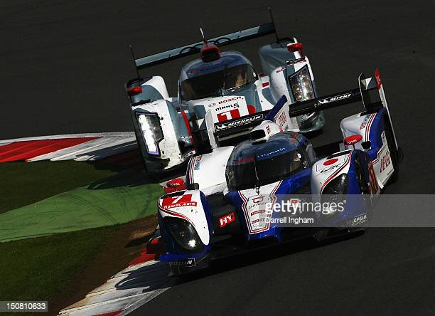 Nicolas Lapierre of France drives the Toyota Racing Toyota TS030 Hybrid ahead of the Audi Sport Team Joest Audi R18 e-tron Quattro driven by Andre...
