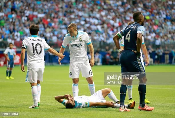 Nicolas Lodeiro and Jordan Morris of the Seattle Sounders look on as teammate Alvaro Fernandez of the Seattle Sounders writhes in pain as Kendall...