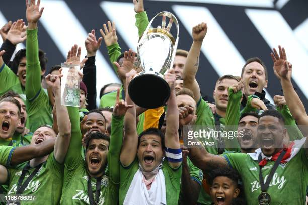 Nicolas Lodeiro of the Seattle Sounders FC holds the trophy and celebrates with his teammates after winning the MLS Cup 2019 against the Toronto FC...