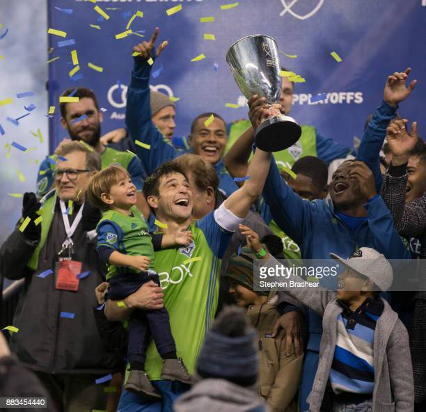 Nicolas Lodeiro of the Seattle Sounders holds up the champsionship trophy and his son while celebrating with other Seattle Sounders after of the...