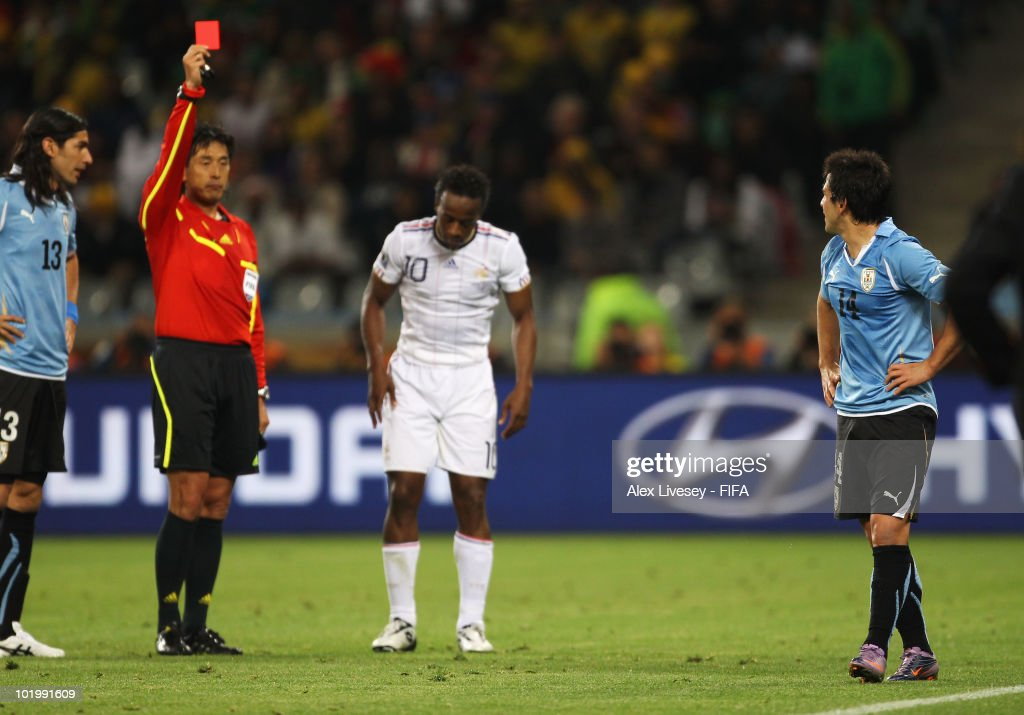Nicolas Lodeiro of Uruguay (L) is shown a red card by Referee Yuichi Nishimura during the 2010 FIFA World Cup South Africa Group A match between Uruguay and France at Green Point Stadium on June 11, 2010 in Cape Town, South Africa.