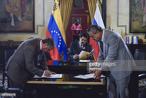 Nicolas Maduro president of Venezuela center looks at documents as Igor Sechin chief executive officer of Rosneft PJSC left and Eulogio del Pino...