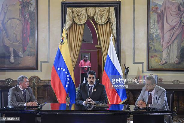 Nicolas Maduro president of Venezuela center speaks to the media as Igor Sechin chief executive officer of Rosneft PJSC left and Eulogio del Pino...