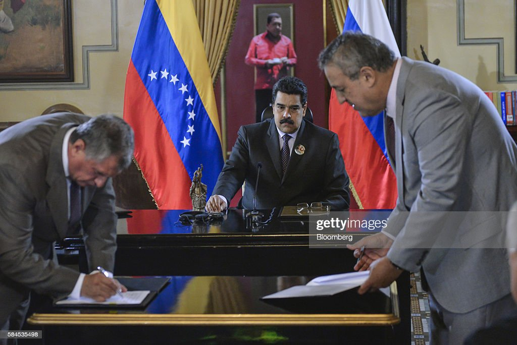 Nicolas Maduro, president of Venezuela, center, watches, as Igor Sechin, chief executive officer of Rosneft PJSC, left, and Eulogio del Pino, president of Petroleos de Venezuela SA (PDVSA) sign natural gas deals in Caracas, Venezuela, on Thursday, July 28, 2016. The agreements included a deal for Rosneft to participate in the Mariscal Sucre natural gas project. Photographer: Carlos Becerra/Bloomberg via Getty Images