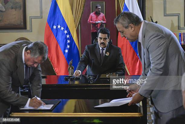 Nicolas Maduro president of Venezuela center watches as Igor Sechin chief executive officer of Rosneft PJSC left and Eulogio del Pino president of...