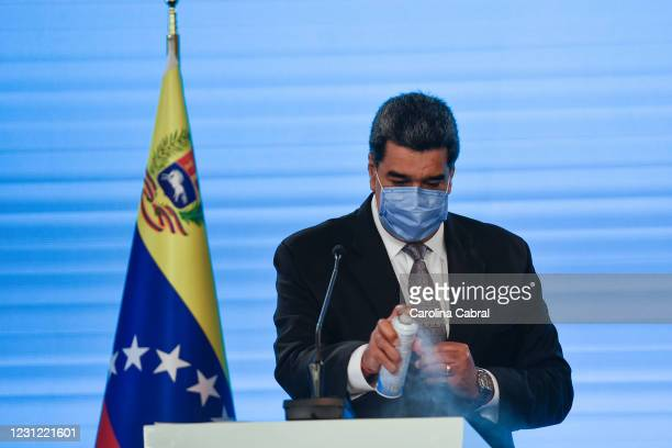 Nicolas Maduro President of Venezuela disinfects his podium with alcohol spray before he speaks in a press conference at Miraflores Palace on...