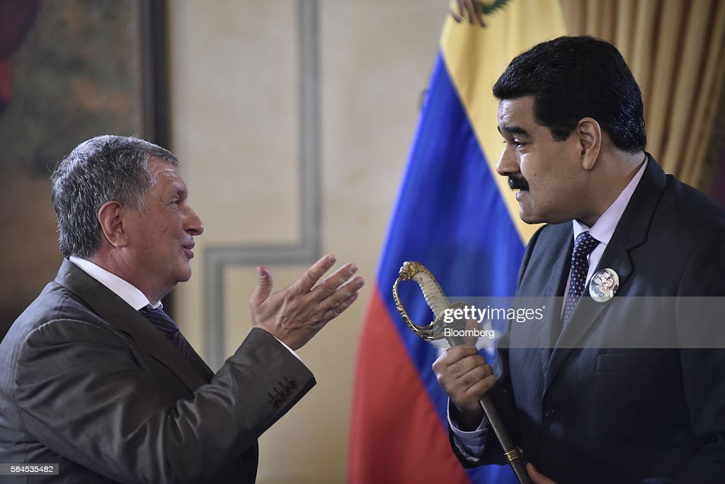 Nicolas Maduro, president of Venezuela, holds a sword given to him as a gift by Igor Sechin, chief executive officer of Rosneft PJSC, left, after Eulogio del Pino, president of Petroleos de Venezuela SA (PDVSA), not pictured, and Sechin signed natural gas deals in Caracas, Venezuela, on Thursday, July 28, 2016. The agreements included a deal for Rosneft to participate in the Mariscal Sucre natural gas project. Photographer: Carlos Becerra/Bloomberg via Getty Images