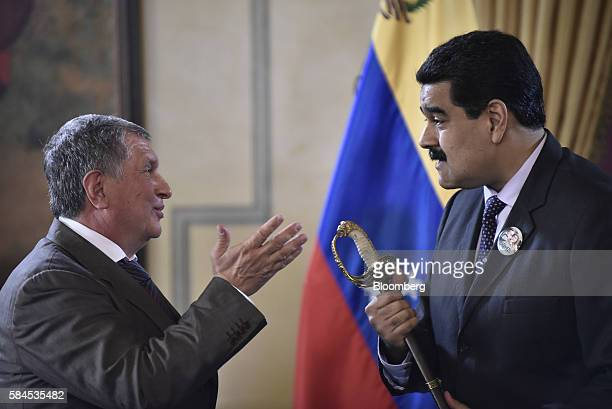 Nicolas Maduro president of Venezuela holds a sword given to him as a gift by Igor Sechin chief executive officer of Rosneft PJSC left after Eulogio...