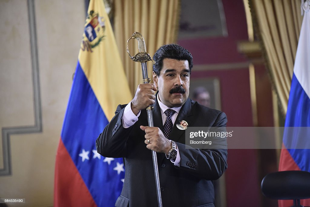 Nicolas Maduro, president of Venezuela, holds a sword given to him by Igor Sechin, chief executive officer of Rosneft PJSC, not pictured, after Eulogio del Pino, president of Petroleos de Venezuela SA (PDVSA), not pictured, and Sechin signed natural gas deals in Caracas, Venezuela, on Thursday, July 28, 2016. The agreements included a deal for Rosneft to participate in the Mariscal Sucre natural gas project. Photographer: Carlos Becerra/Bloomberg via Getty Images