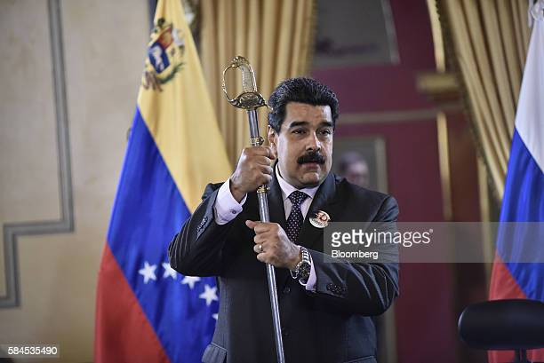 Nicolas Maduro president of Venezuela holds a sword given to him by Igor Sechin chief executive officer of Rosneft PJSC not pictured after Eulogio...