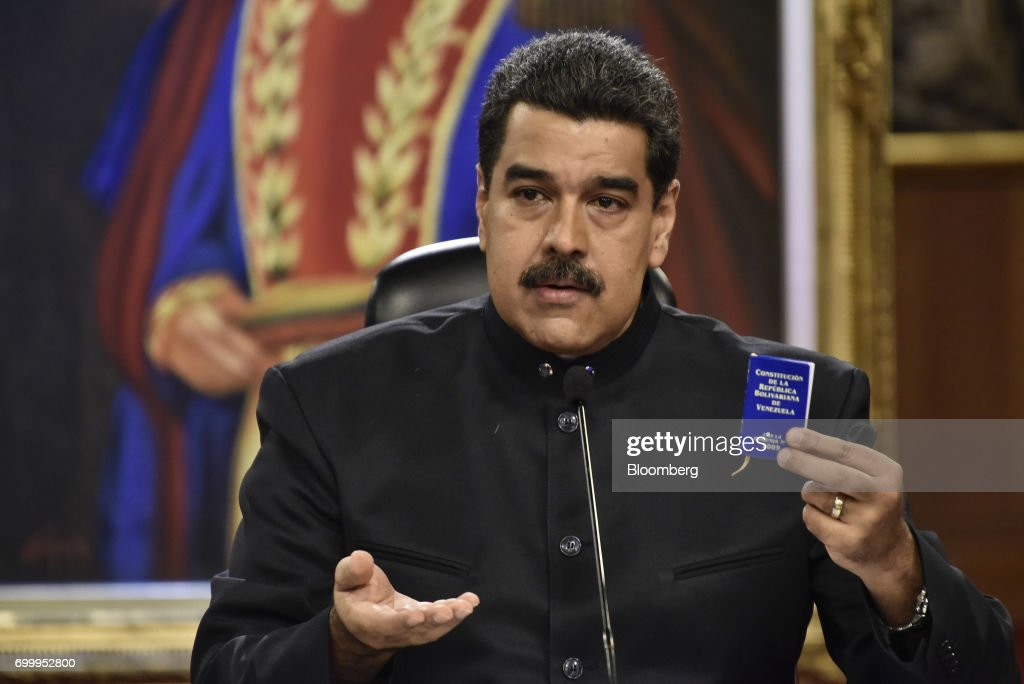 Nicolas Maduro, president of Venezuela, holds up a copy of the Venezuelan constitution during a press conference in Caracas, Venezuela, on Thursday, June 22, 2017. Since June 15, Maduro has named four new ministers: Mirelys Contreras as Prisons Minister; Ana Reyes as Culture Minister; Kyra Andrade as Communes Minister; Yamilet Mirabal Calderon as Indigenous Peoples Minister; and Samuel Moncada as foreign minister. Photographer: Carlos Becerra/Bloomberg via Getty Images